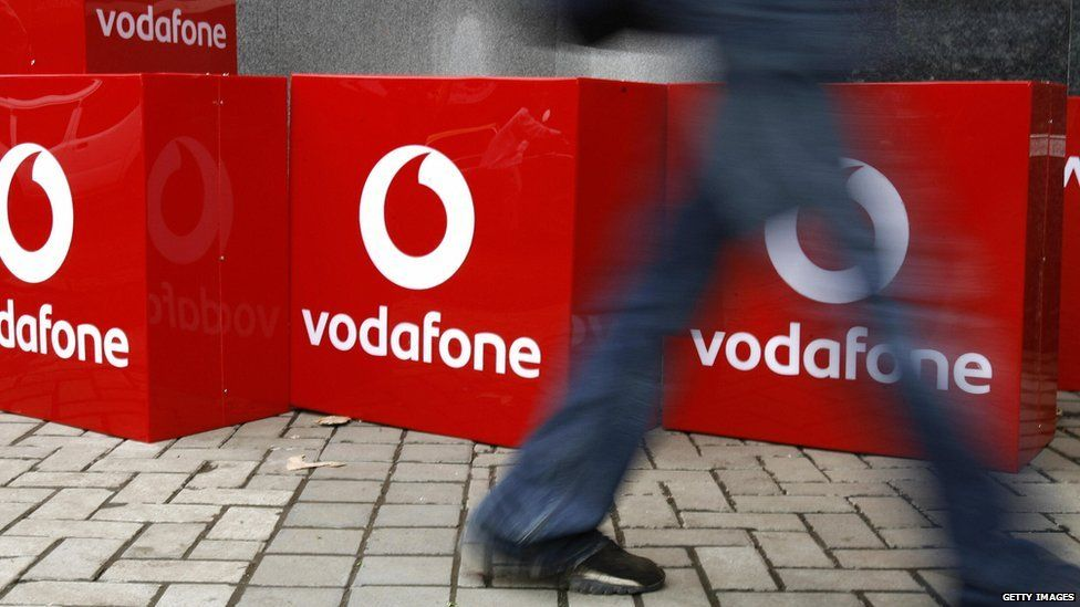Person walking in front of Vodafone logos