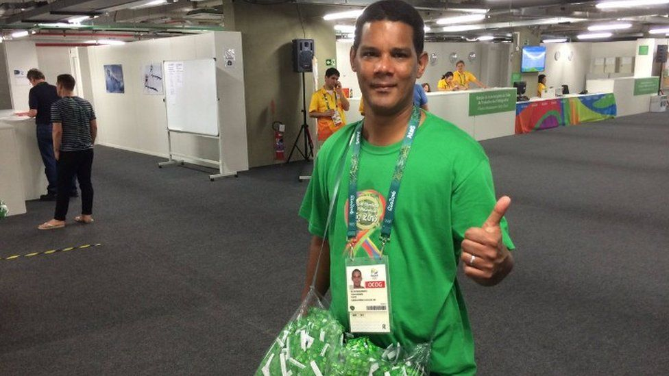 Man hands out condoms at the Olympic village in Rio