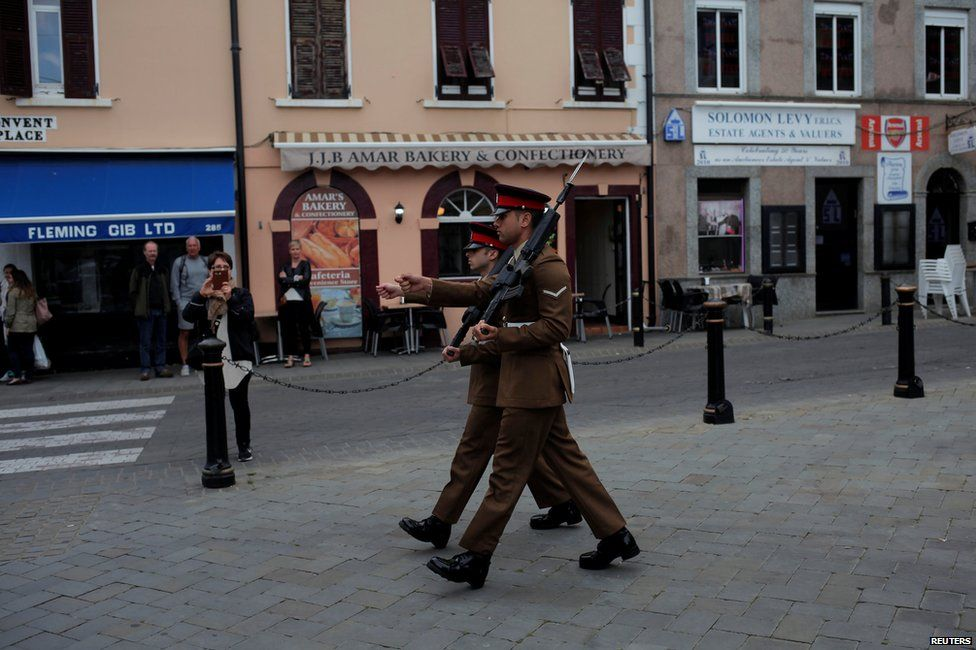 Soldiers walk during a change of guard outside the Convent building in Gibraltar