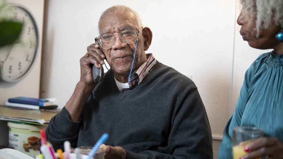 An elderly man talking on the telephone