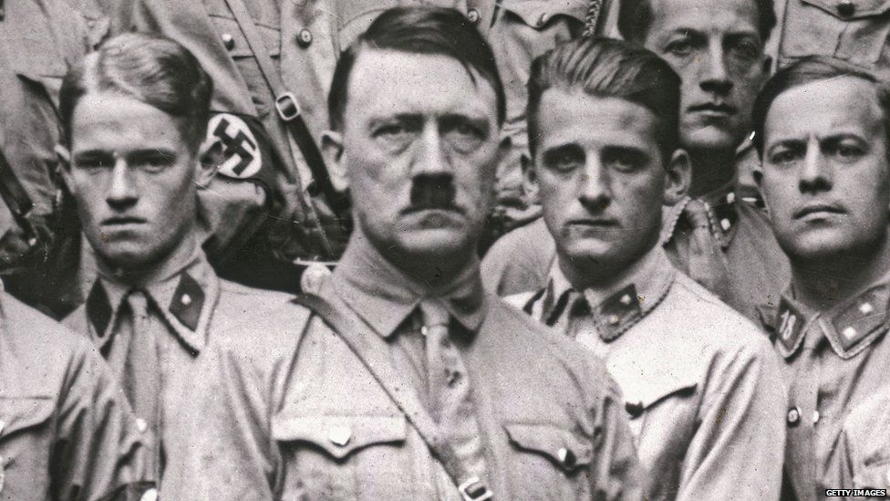 Adolf Hitler standing in front of other men