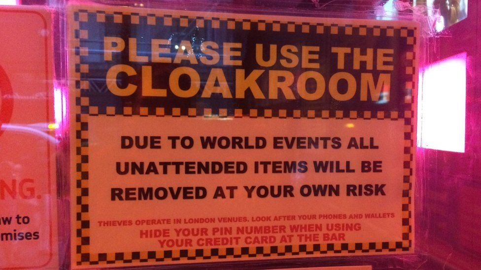 A cloakroom sign which reads: 'Due to world events all unattended items will be removed at your own risk'