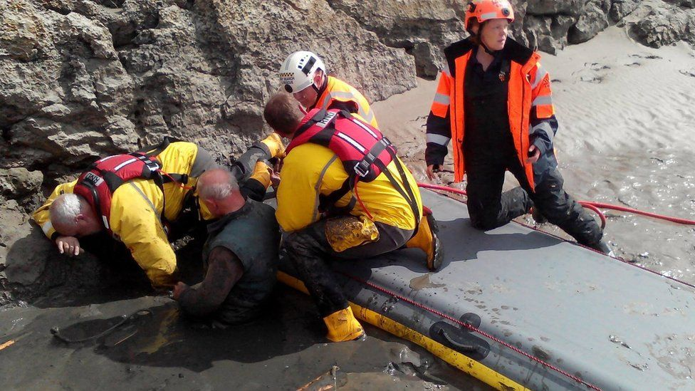Rescuers struggle to free the man from the quicksand