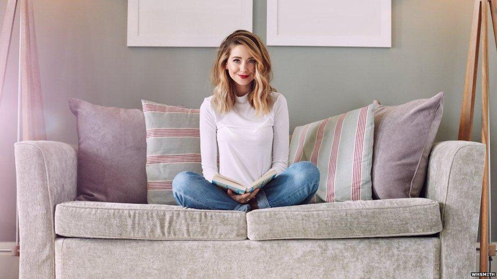 Zoella sitting on the sofa with a book