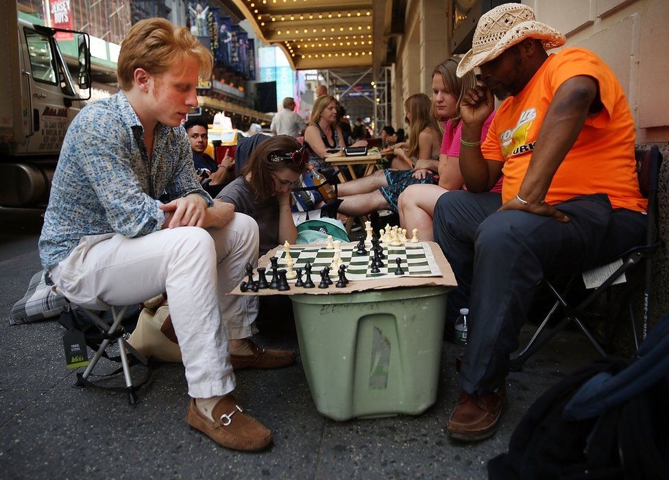 People playing chess in the queue for return tickets to Hamilton in New York in 2016