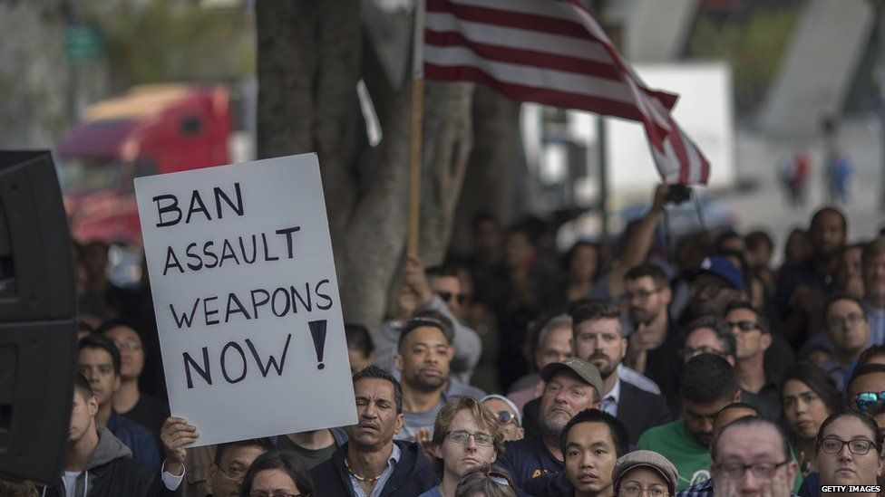 Protesters gathered holding a sign saying: Ban assault weapons now