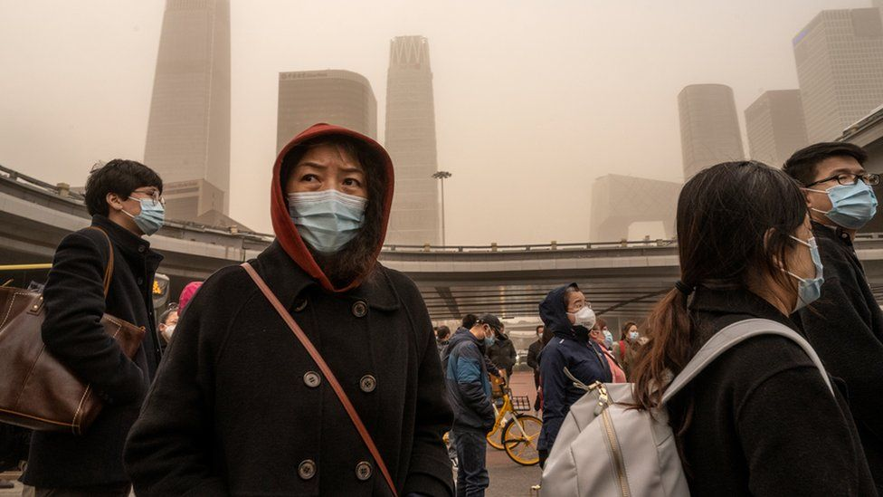 Commuters wear protective masks as they leave work in the Central Business District during a sandstorm on 15 March 2021 in Beijing