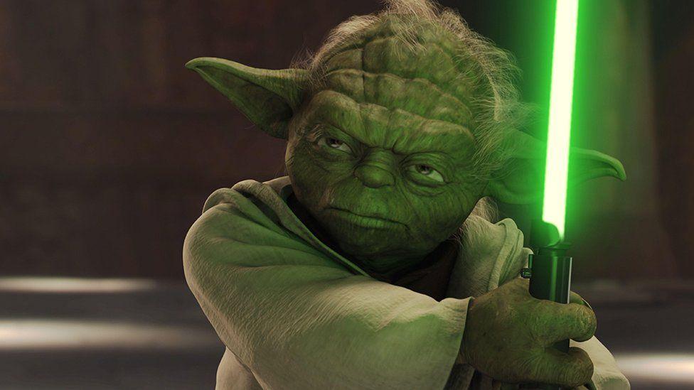 Yoda wielding a lighsaber