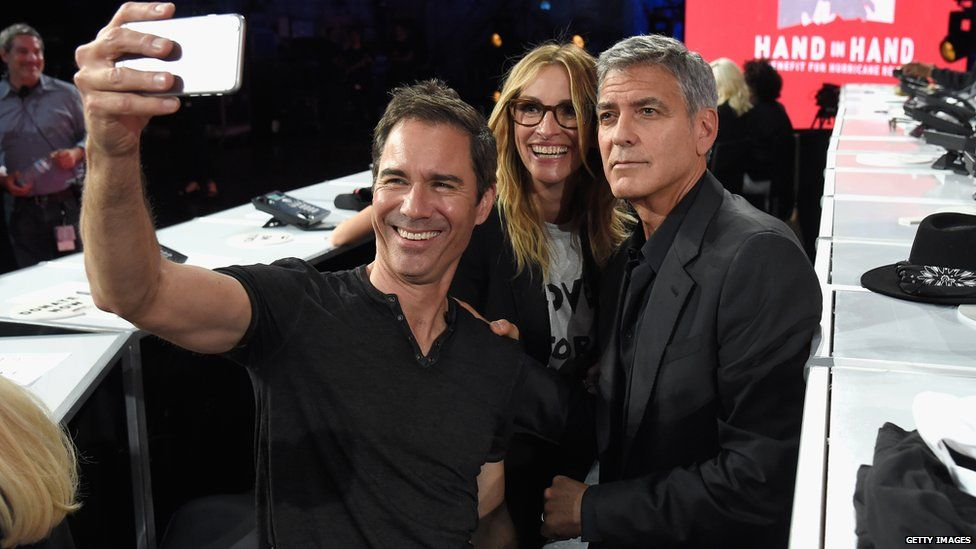Will & Grace actor Eric McCormack takes a selfie with George Clooney and Julia Roberts at the telethon in L.A.