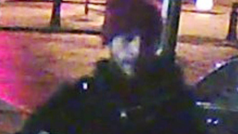 CCTV image of a man with a read hat on