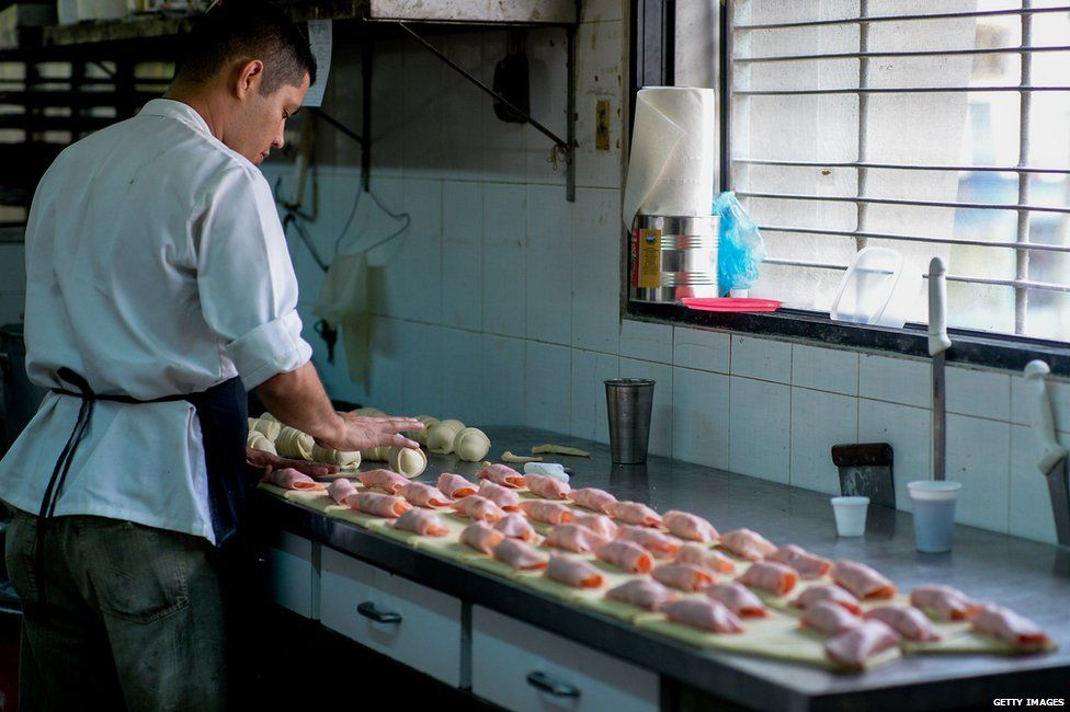 Baker making ham croissants in Venezuela