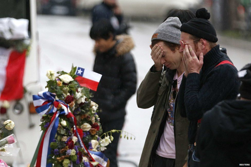 Eagles of Death Metal looking at floral tributes to those killed at the Bataclan