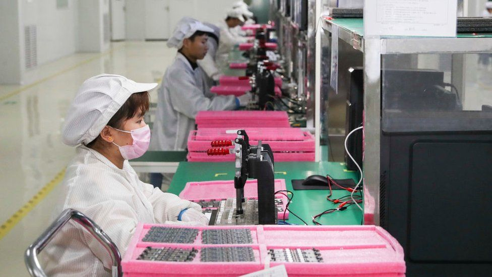 Employees work on the assembly line of printed circuit board for smartphone in Jiangsu Province of China.