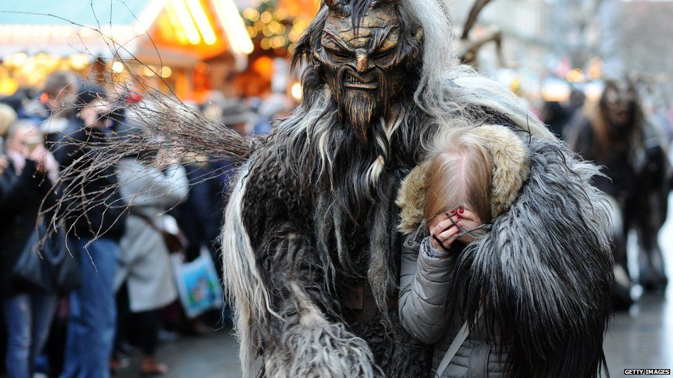 This is a photo of a man dressed as Krampus while holding a woman during the traditional German Christmas festival.
