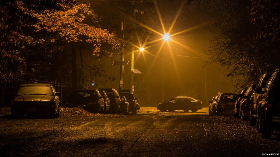 Cars parked in the dark under a streetlight