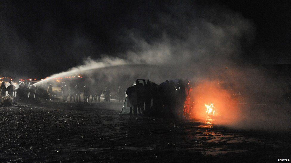 This is a photo of police using a water cannon to put out a fire started by protesters.