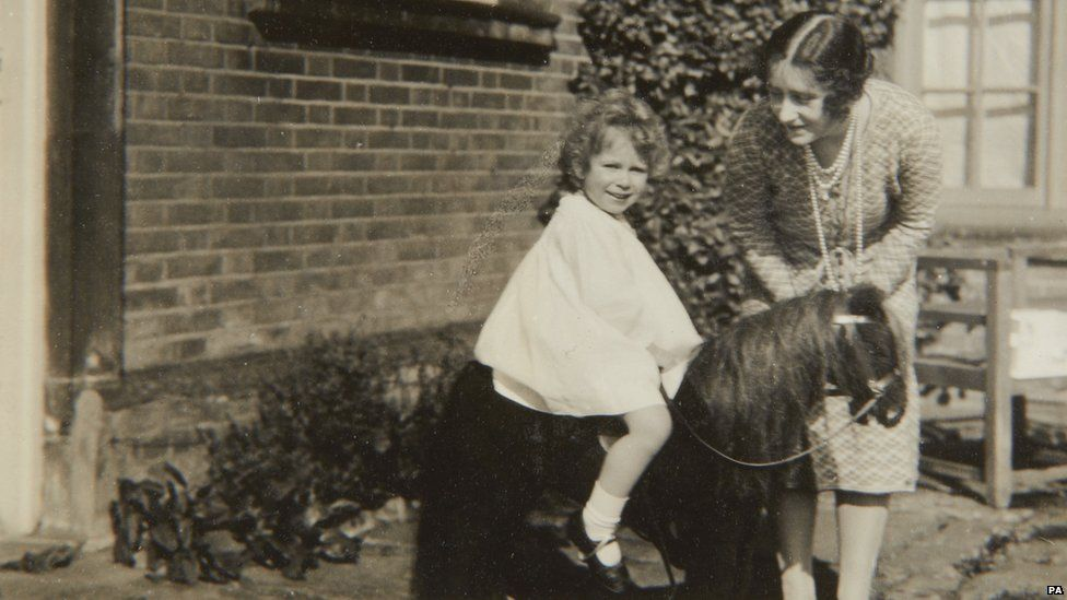 Queen Elizabeth II with a toy horse in front of Naseby Hall 1928