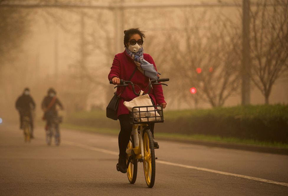 A woman cycles along a street during a sandstorm in Beijing on 15 March 2021