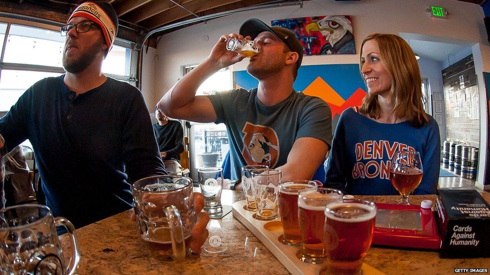 Fans drink beer while watching the Denver Broncos