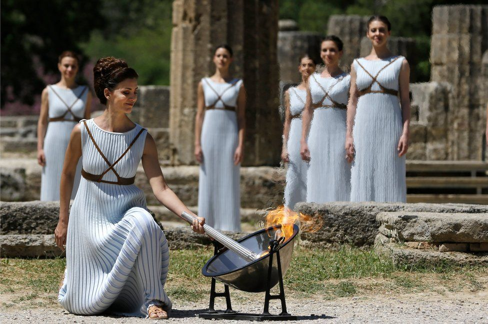 Greek actress Katerina Lehou, playing the role of High Priestess, lights the torch