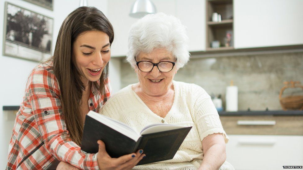 A young woman and an old woman looking at a photo album