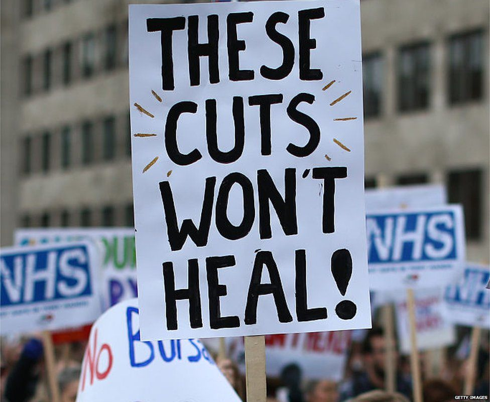 """A placard from an NHS protest saying: """"These cuts won't heal"""""""