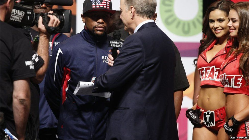Picture of Janira next to Floyd Mayweather at a weigh in event