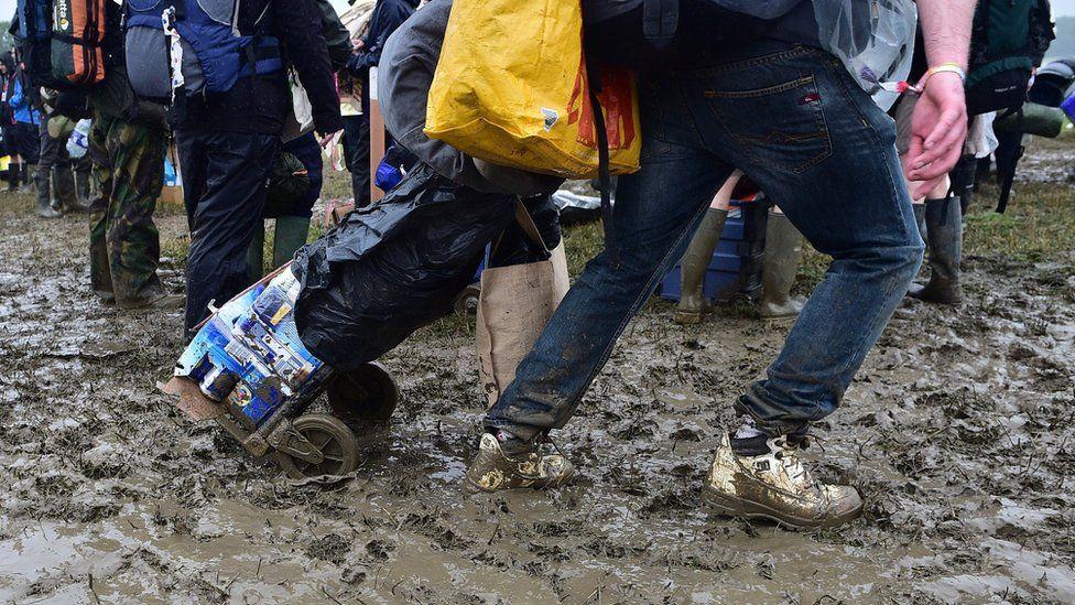 Man pulling a cart through mud