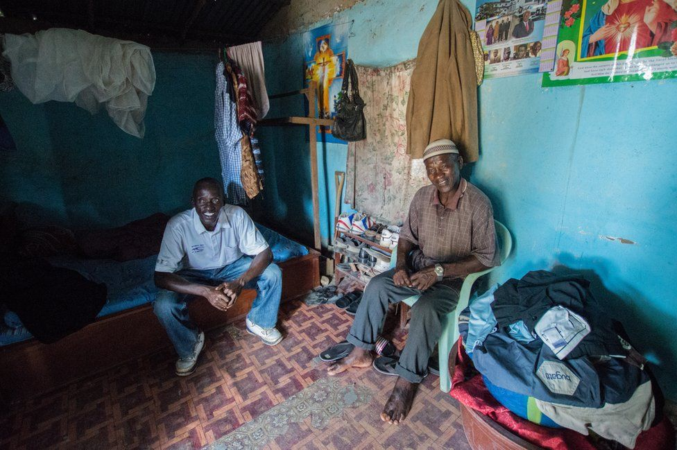 Two men sit inside their house smiling for the camera