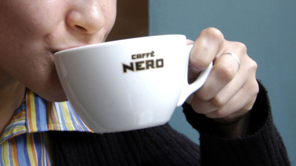 Woman drinking out of a Caffe Nero cup