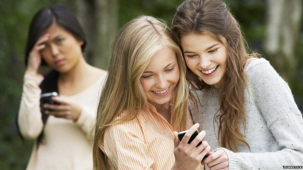 Two girls smiling and looking at a phone while another looks sad