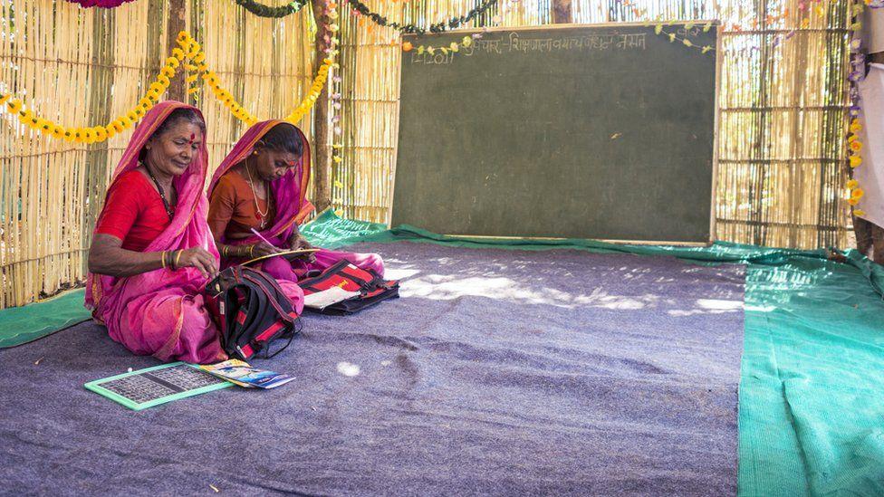 two women in the classroom, cross-legged on the floor in front of a blank blackboard
