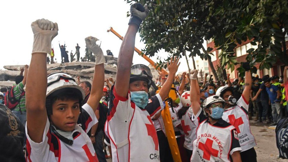 Red Cross workers hold their hands up for silence