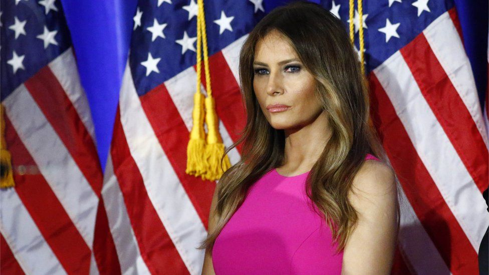 Melania Trump standing in front of an American flag