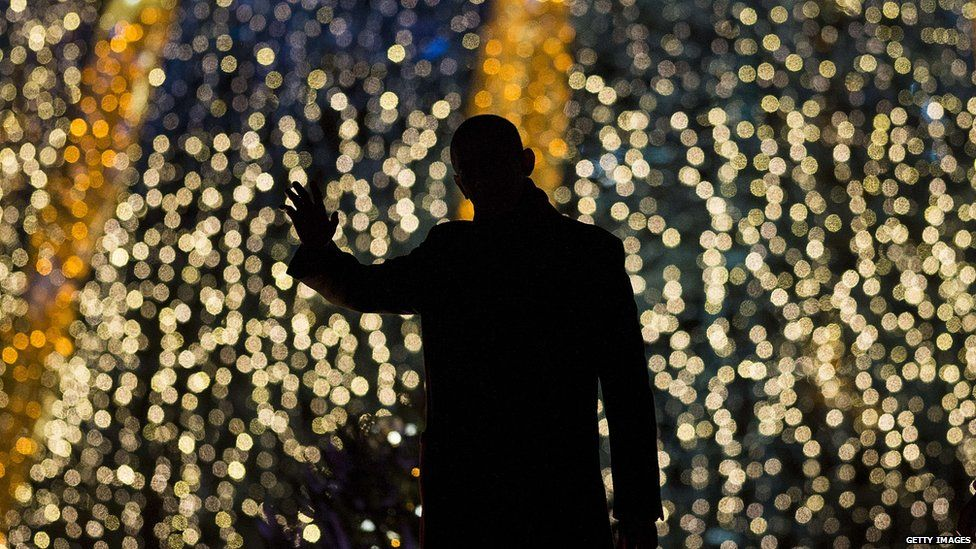 Barack Obama in front of a Christmas tree with lights
