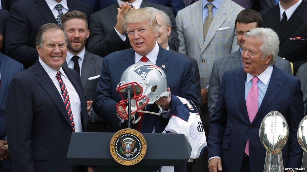 President Trump holding an American football helmet