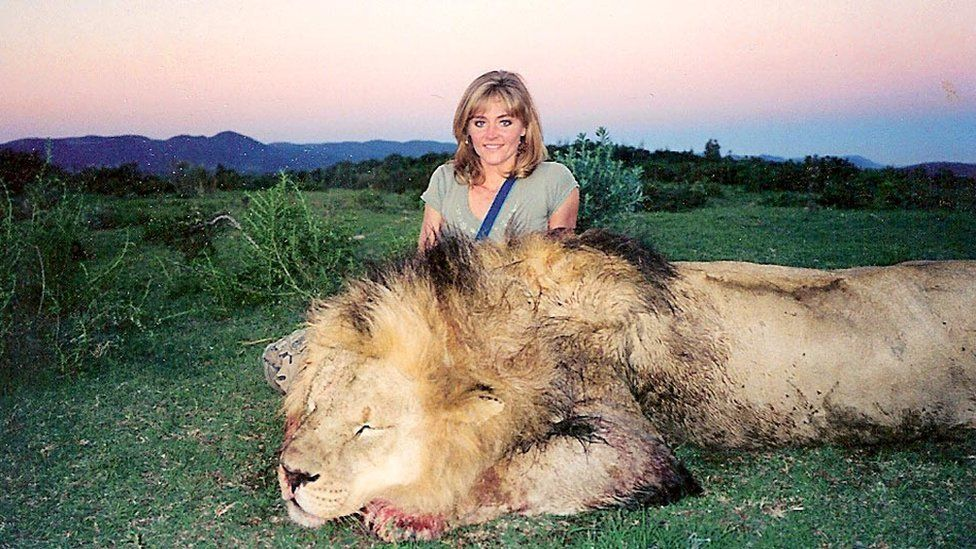 Rebecca poses with a dead lion
