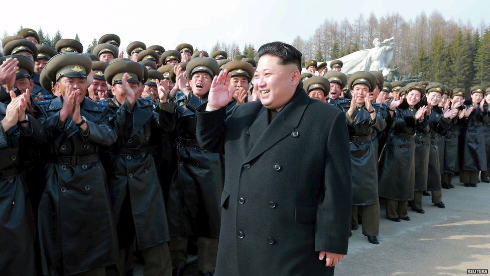 Kim Jong-Un, walking in front of troops, on top of a mountain