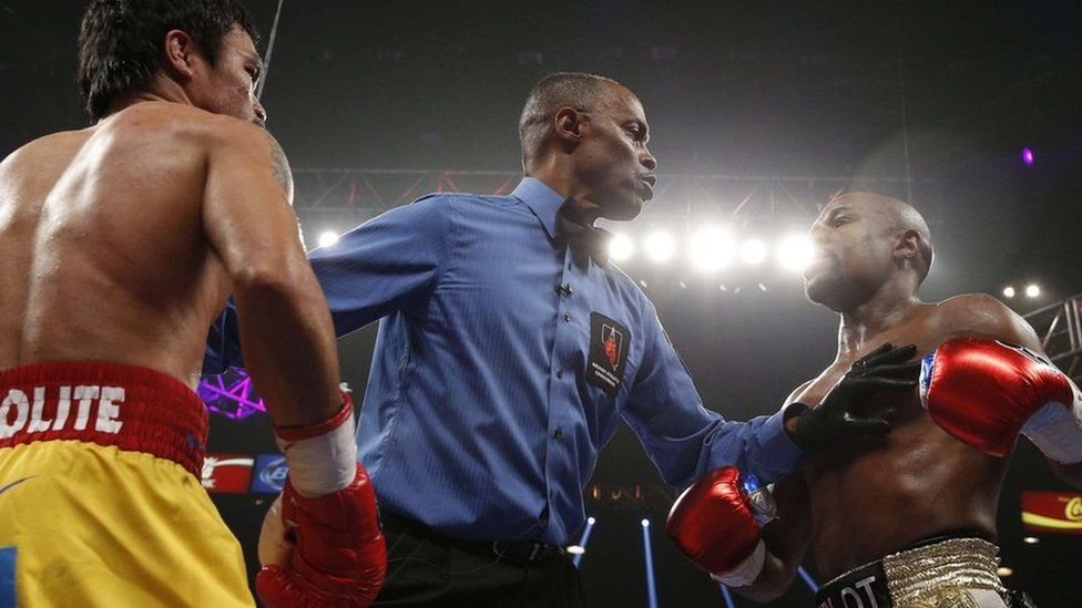 The referee splits US boxer Floyd Mayweather Jr., (R) and Manny Pacquiao