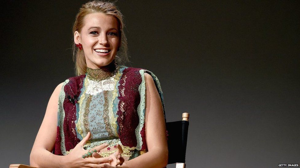 Blake Lively smiling, sitting in a chair ahead of an event in New York