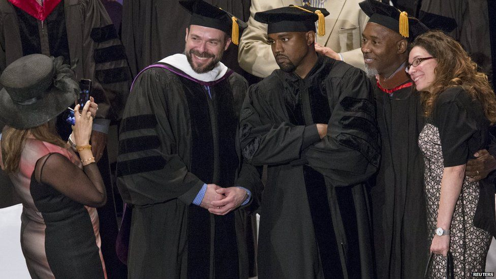 Kanye West posing for photos after being given his honorary doctorate degree.