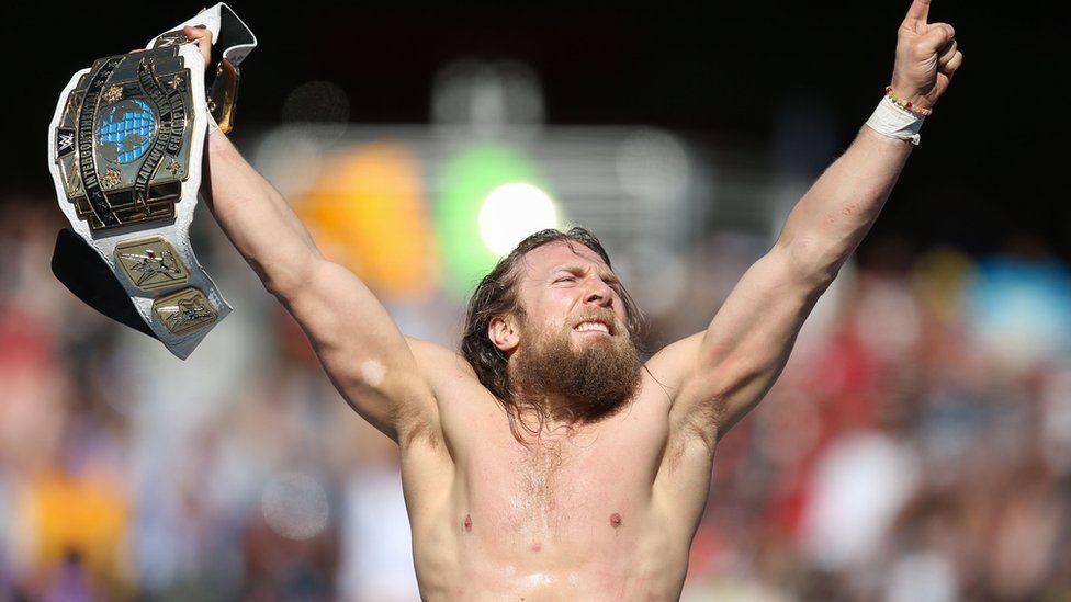 Daniel Bryan holding a belt in the air