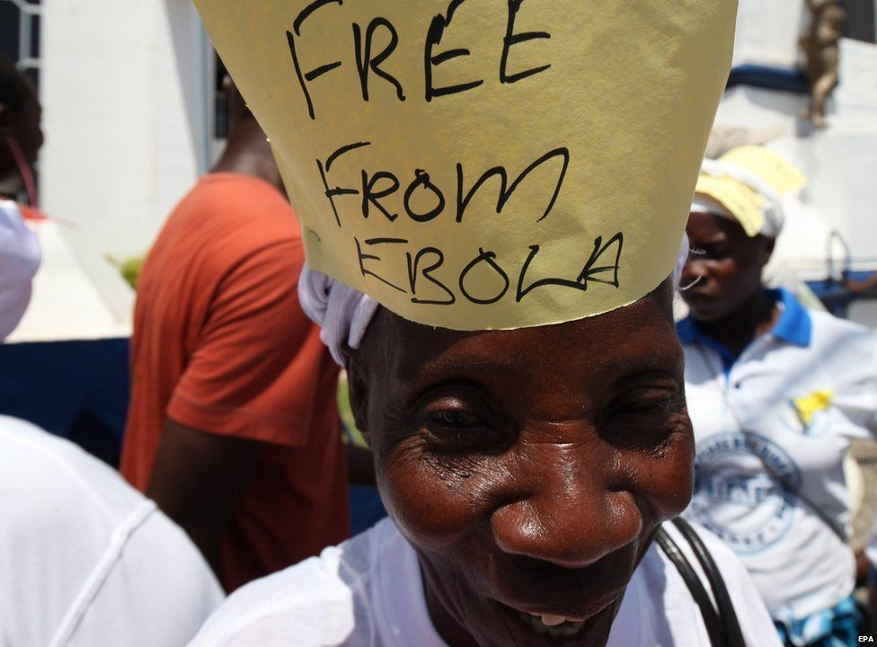 "A woman smiles with a sign saying ""Free from Ebola"" on her head"