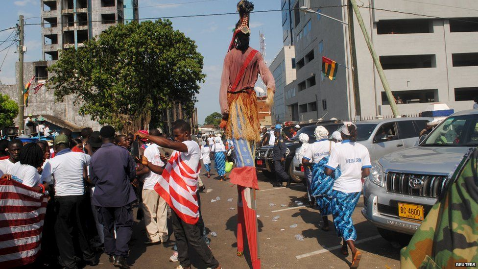 A person walks on stilts through the street