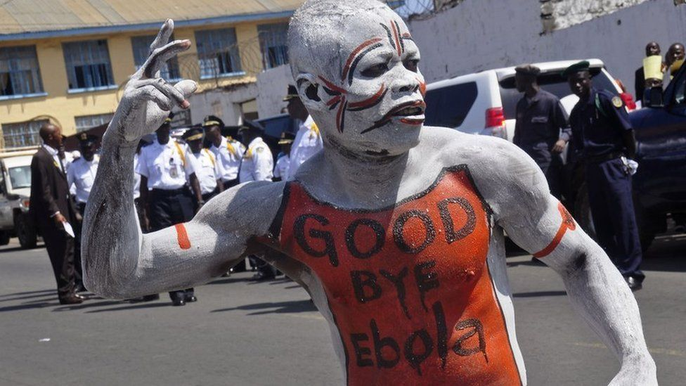 "A man dances in body paint with the words ""Good Bye Ebola"" on his chest"