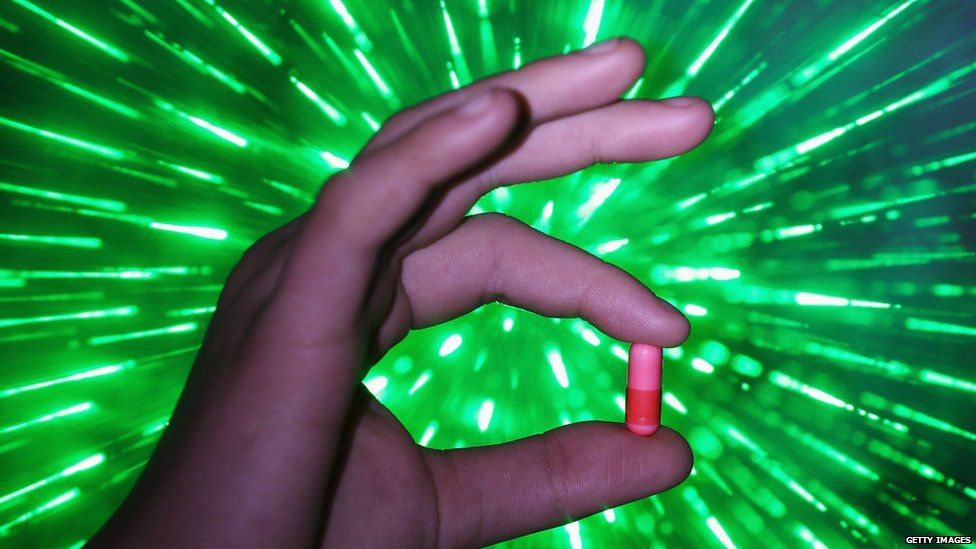 A hand holds up a pill in a Manchester head shop