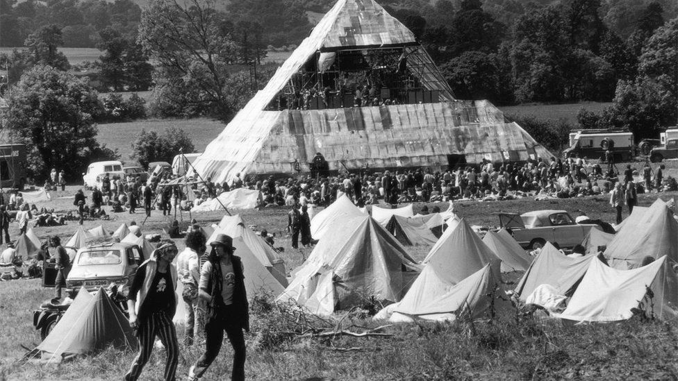 Tents and people in front of the Pyramid Stage