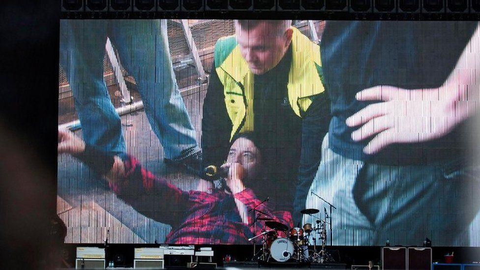 Dave Grohl is shown on the TV screen after his fall