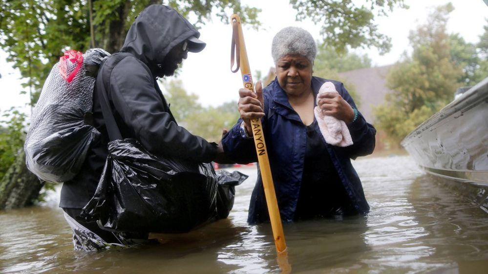 Andrew Mitchell helps his neighbor Beverly Johnson onto a rescue boat to escape the rising flood waters from Tropical Storm Harvey in Beaumont Place, Houston, Texas, U.S., on August 28, 2017.