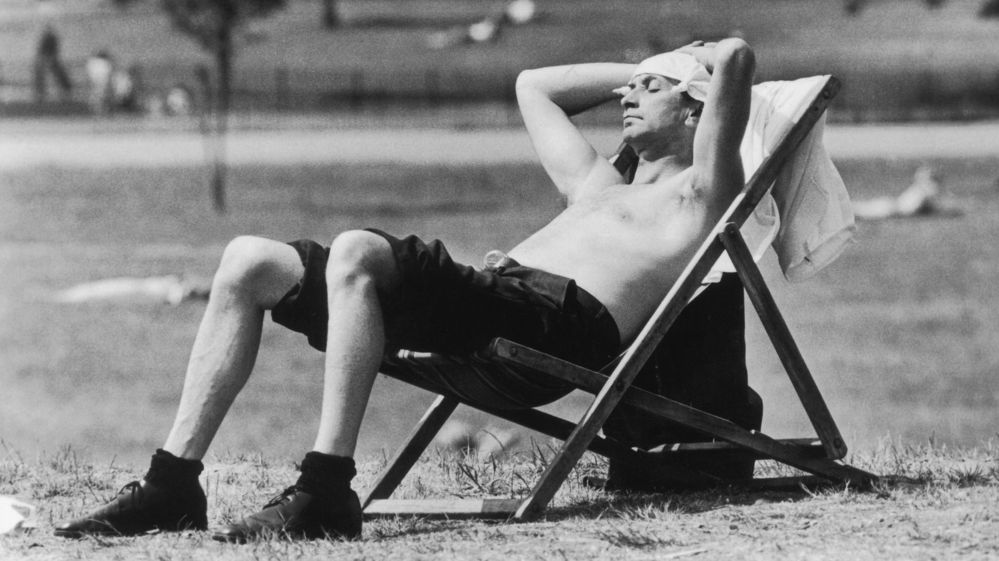 A man sunbathes on a deckchair in Kensington Gardens